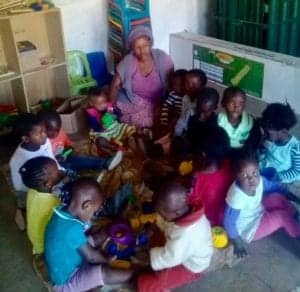Nosandile Bangani with some of the children she looks after in a shearing shed at the Zukhanye Day Care Centre.