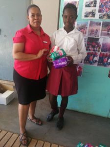 Sister Mirriam Sepeng from the OVR clinic hands sanitary towels over to one of the learners at the school.