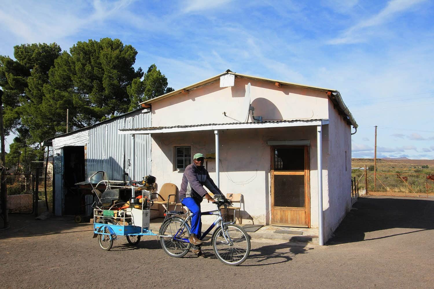Max Ndamane, with the bicycle-drawn trailer he made for his gardening services in Richmond, in front of the old ramstal he turned into a home. Photo: Chris Marais