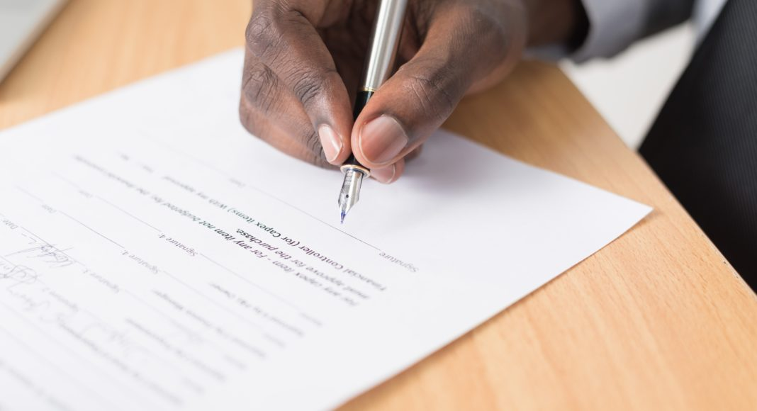 Man signing a contract. Unsplash picture