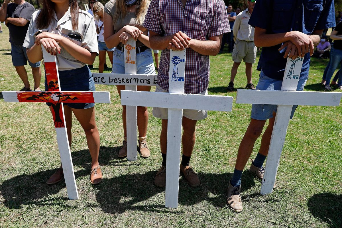 Farmers hold white crosses during an earlier protest against farm murders and attacks. Residents are anxiously awaiting the implementation of the rural safety strategy. Photo: Phill Magakoe/AFP via Getty Images