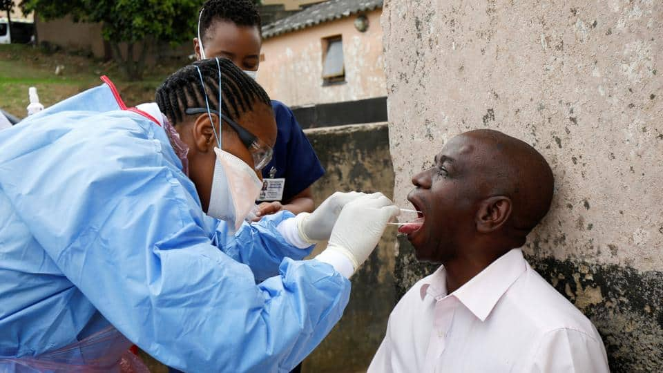 A health worker wearing a protective suit takes a swab from a resident during earlier door-to-door testing in an attempt to contain the coronavirus disease outbreak, in Umlazi township near Durban. Photo: AFP
