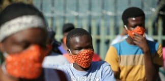 Community members wearing protective face masks as they queue for aid in Zandspruit informal settlement, north of Johannesburg. Phill Magakoe/AFP via Getty Images