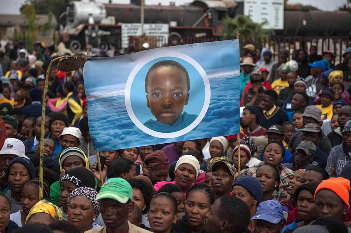 Coligny residents during an earlier march with a childhood image of Faki Mosweu. Photo: International Business Times
