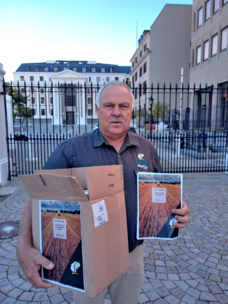 Free State Agriculture president Francois Wilken outside Parliament with some of the 80 000 signatures the agricultural powerhouse handed in against the Expropriation Bill. Photo: Supplied/Food For Mzansi