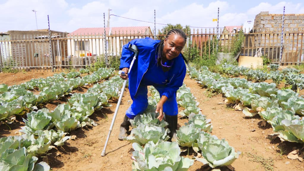 Maikaheng Moeling (56) suffered a stroke in 2001 and is currently farming while walking in crutches and using only one hand. She grows vegetables at the Katlehong Customer Care Centre in Gauteng. Photo: Funiwe Ngwenya/Food For Mzansi