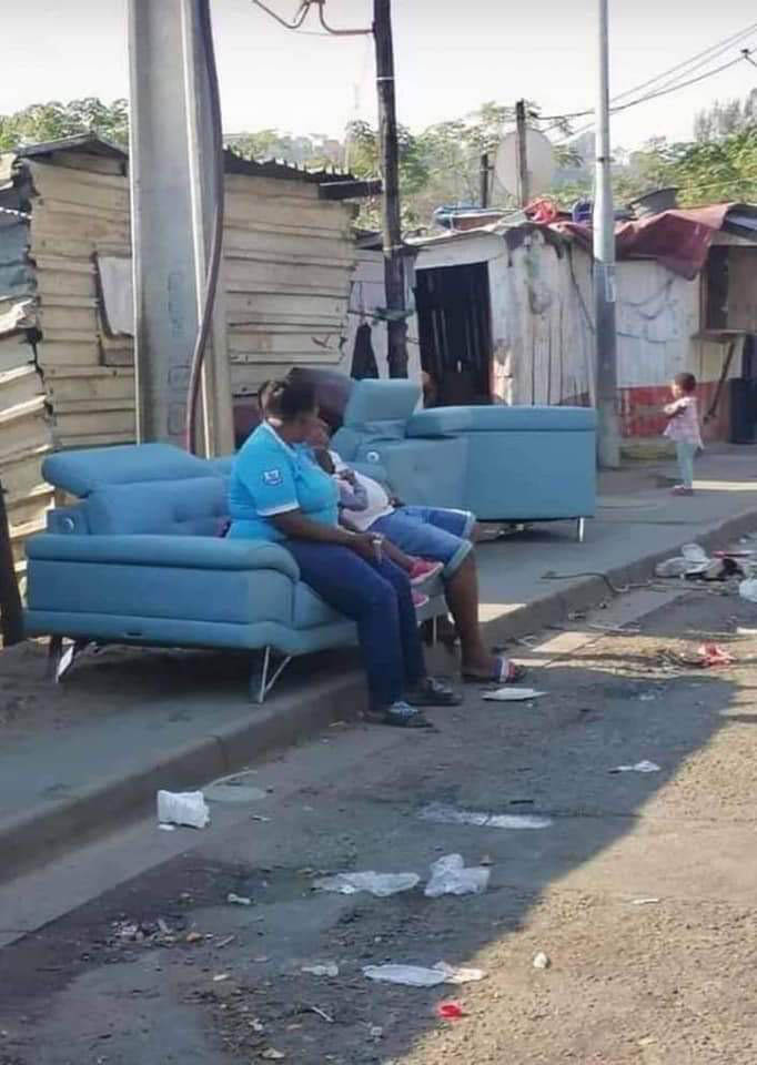 This picture, showing two women sitting on an expensive leather sofa, has gone viral as looting has ticked up in the country. Photo: Supplied/Food For Mzansi