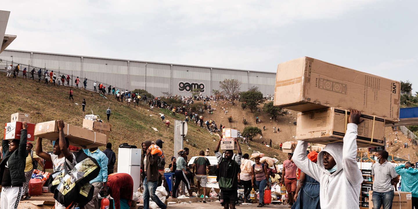 Suspected looters carry goods from the Game Warehouse in Durban on 13 July 2021. President Cyril Ramaphosa deployed troops in a bid to quell unrest that has claimed at least 50 lives. Photo: AFP