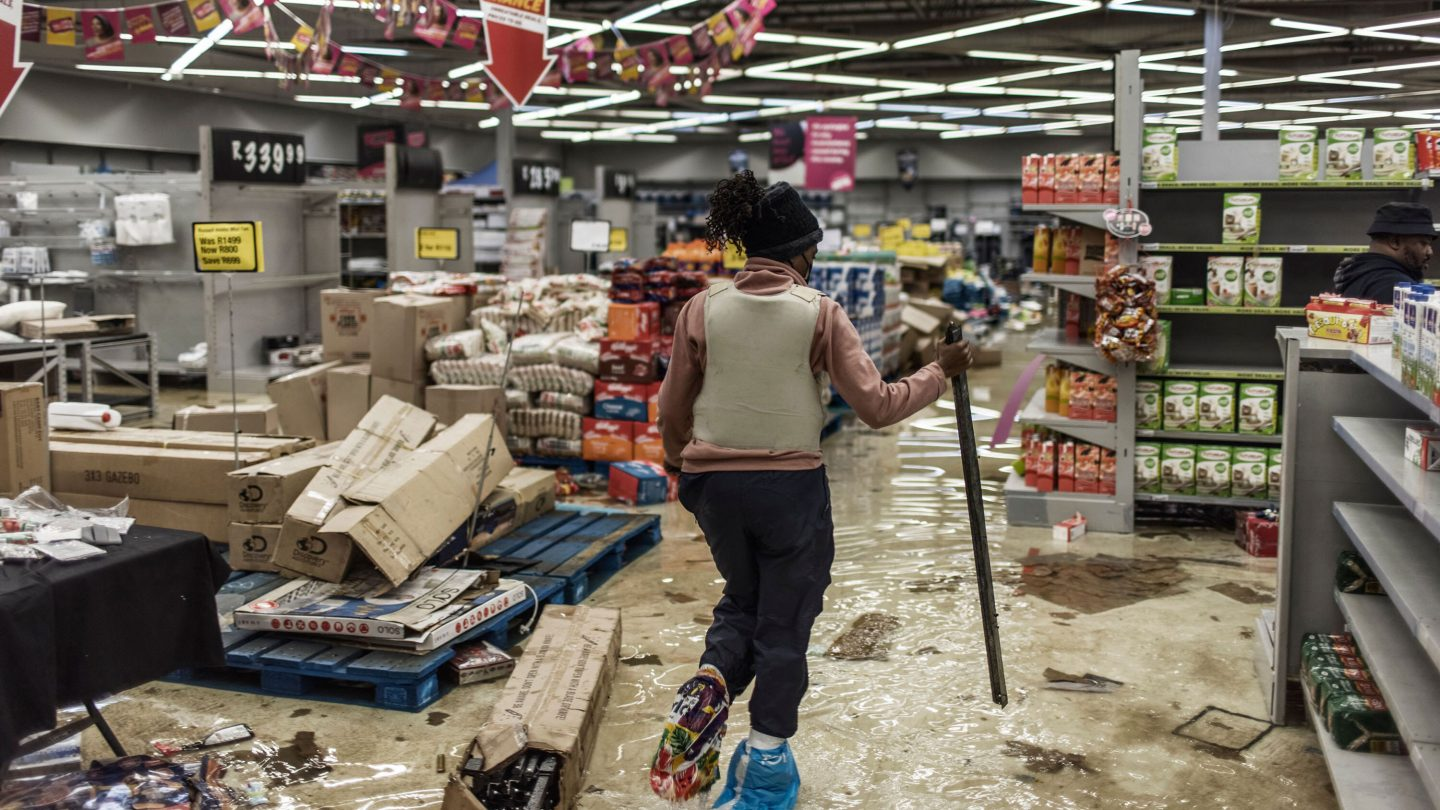 A police officer inspects the damage at one of the recently looted malls in Gauteng. Photo: Getty Images